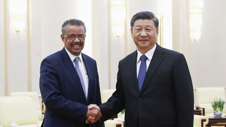 Chinese President Xi Jinping shakes hands with World Health Organization (WHO) Director-General Tedros Adhanom Ghebreyesus.