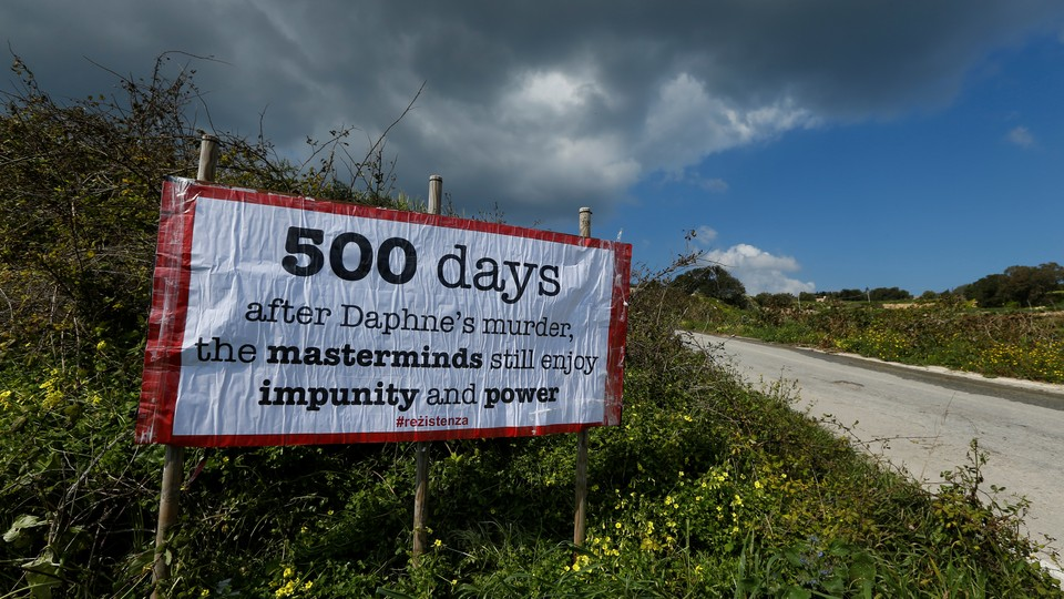 """A sign reading """"500 days after Daphne's murder, the masterminds still enjoy impunity and power"""" marks the location of Daphne Caruana Galizia's murder."""