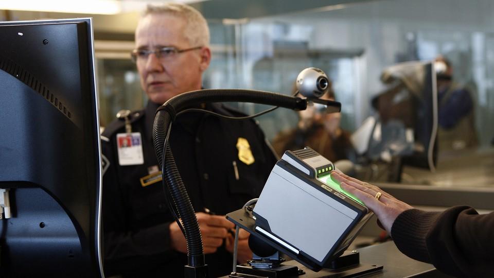 A traveler scans their fingerprints at an airport checkpoint.