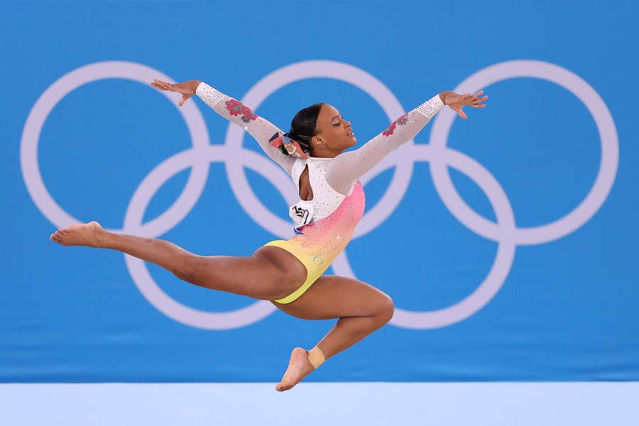 A gymnast leaps in the air in front of a rendering of the Olympic rings.