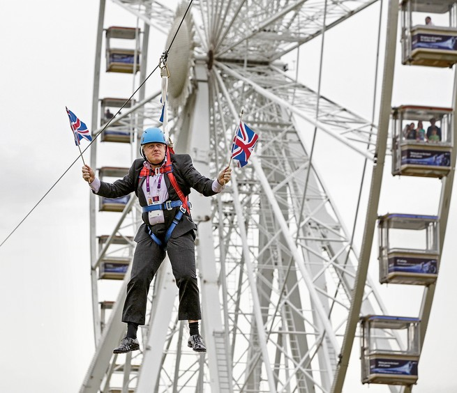 Photo: Boris Johnson holding two flags while hanging in harness from zipline, with London Eye ferris wheel in background