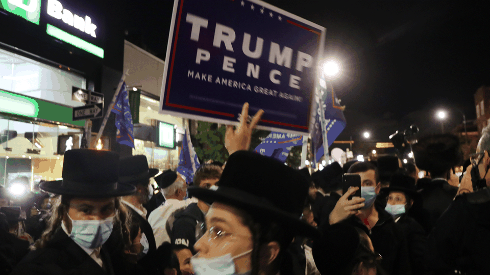 A protester holds up a Trump-Pence sign.
