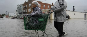 A woman in a raincoat pushes her daughter in a shopping cart across a flooded street