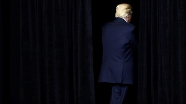 Donald Trump exits a dark stage.