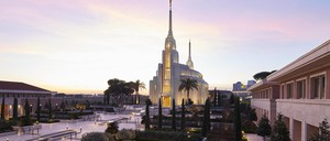 A Mormon temple with two spires, at dusk.