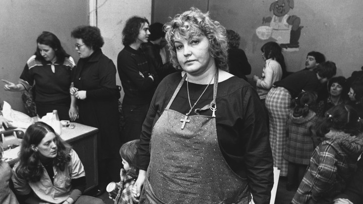 Activist Erin Pizzey stands in a room crowded with other women.