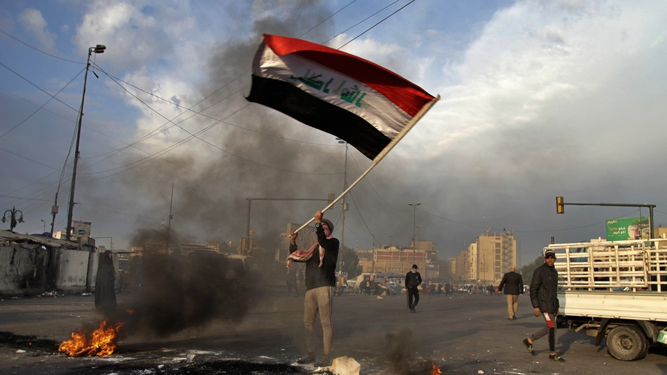 Protester waving Iraq flag after missile strike in Baghdad