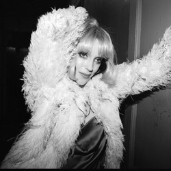 A black-and-white picture of a blonde St. Vincent in a fluffy jacket