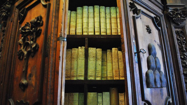 Green and red lighting reveals several books on wooden shelves