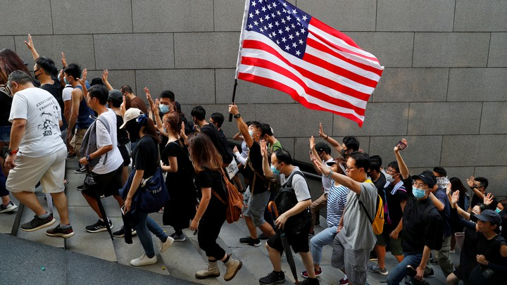Hong Kong protesters hold up five fingers and brandish an American flag during a march.