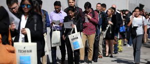 People wait in line, holding tote bags in the sunshine, outside a job fair.