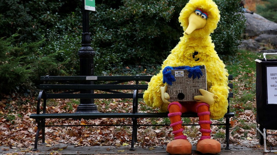 A man dressed as Big Bird from Sesame Street sits alone on a park bench.