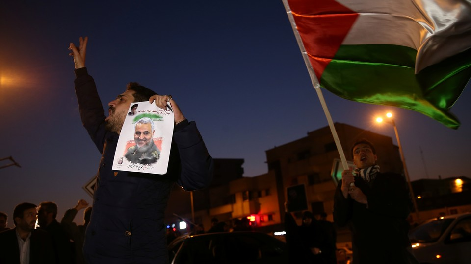 A man holds a photo of Qassem Soleimani, surrounded by others on a dark street in Tehran, celebrating after Iran launched missiles at U.S. forces in Iraq.
