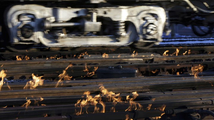 A train moves past rails surrounded by flames.