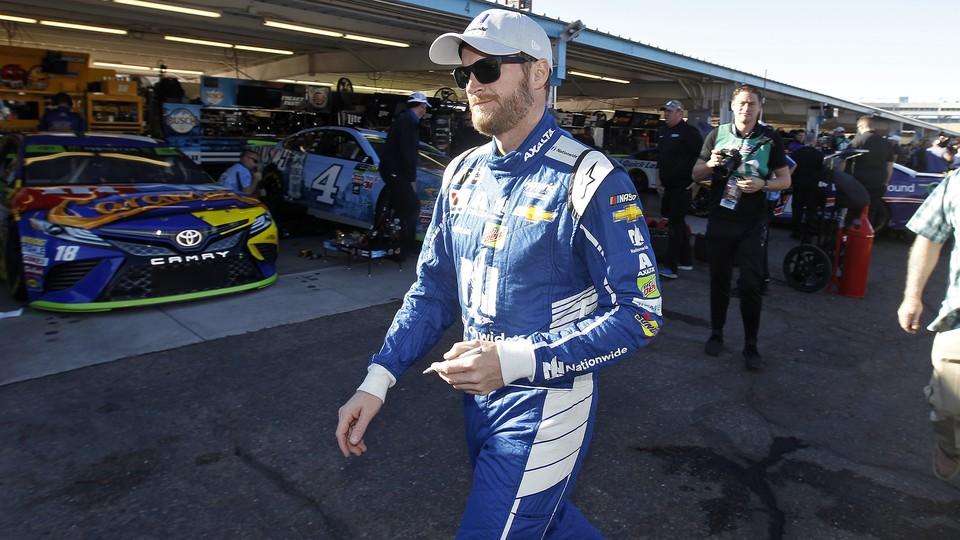 Dale Earnhardt Jr. walks through the garage area before practice for the NASCAR Cup Series auto race at Phoenix International Raceway