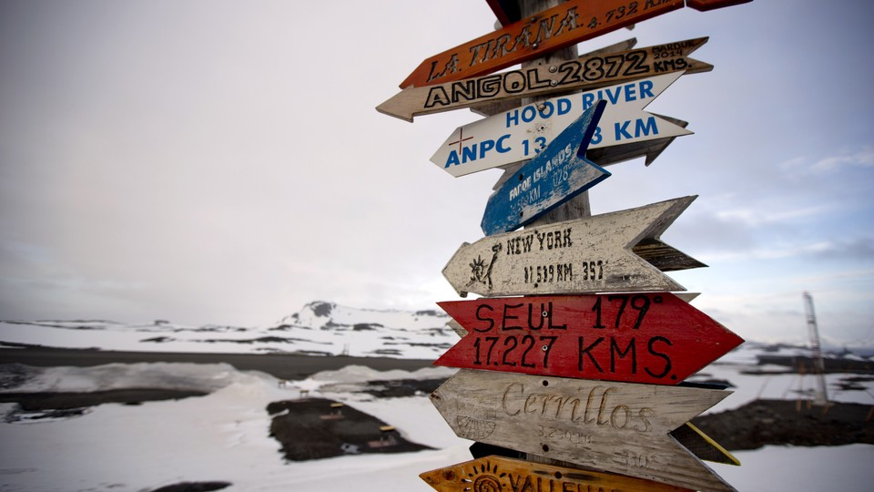 A signpost with the distances to various destinations against a snowy background