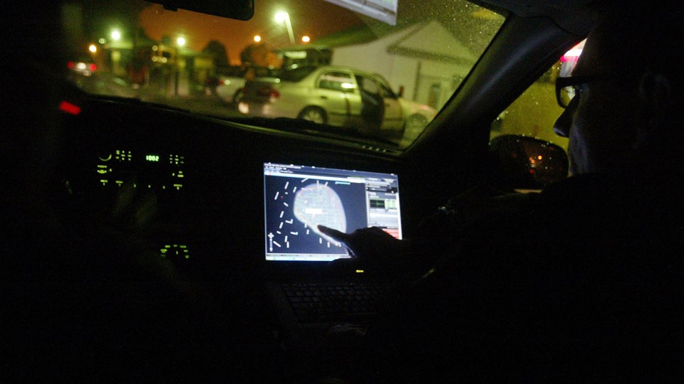 A person points at a GPS inside a vehicle on a residential street.