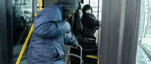 photo: A bus driver in Ohio wears a protective mask as a passenger boards on March 17.