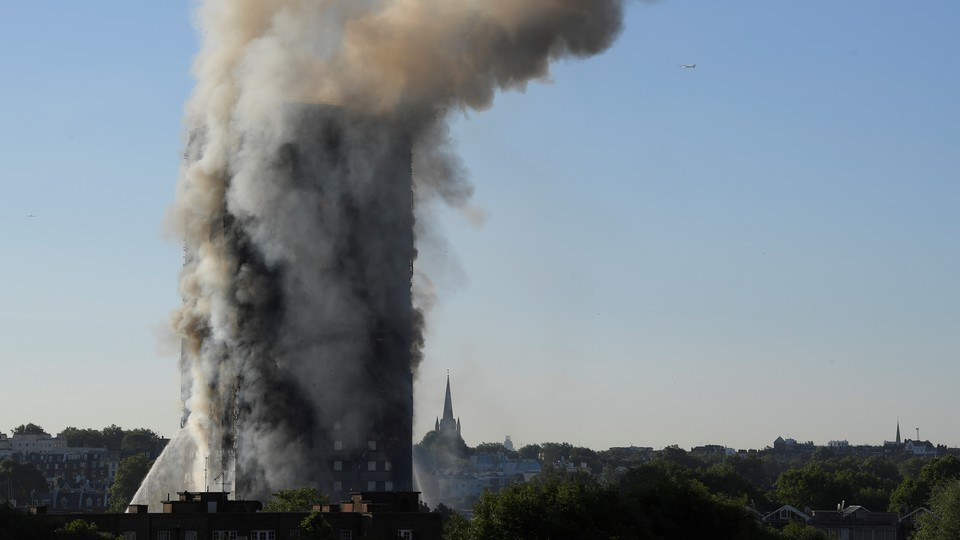 Smoke billows as firefighters deal with a serious fire in a tower block at Latimer Road in West London on June 14, 2017.