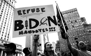 """A woman holds a sign reading """"Refuse Biden mandates!!!"""""""