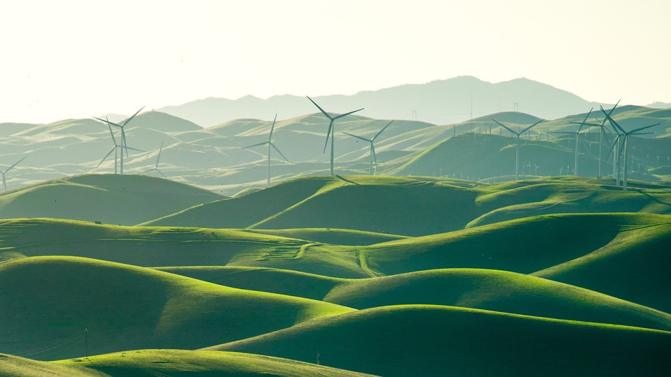 Wind turbines spin over a Elysian landscape of green fields