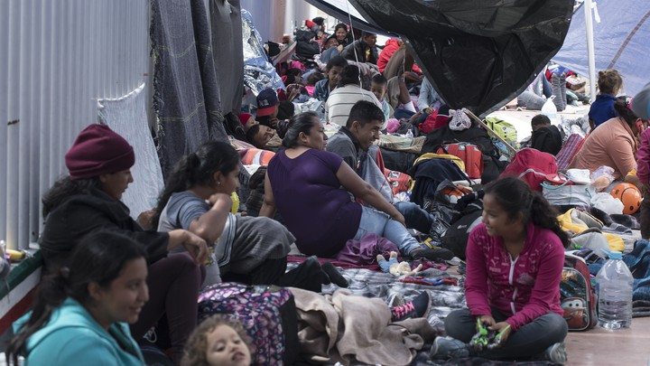 Members of the caravan await entry into the United States