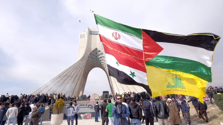 A man carries a giant flag made of flags of Iran, Palestine, Syria and Hezbollah in Tehran.