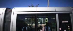 a photo of a woman riding a light rail train in Jerusalem.