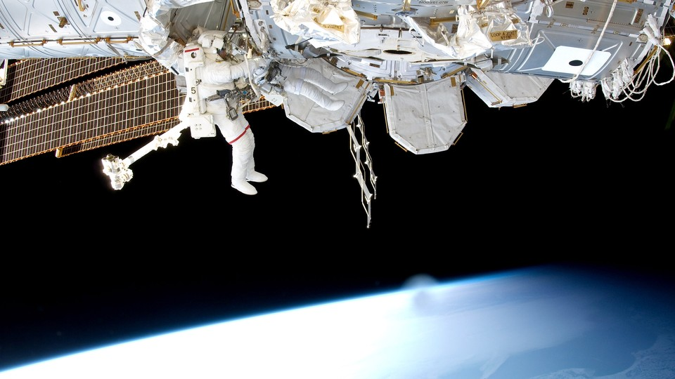 An astronaut works on the outside of the International Space Station