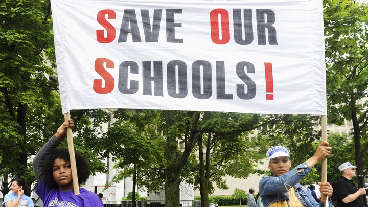 """Students of the East Ramapo School District hold a sign that reads """"Save our schools!"""""""