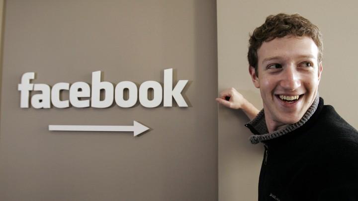 Mark Zuckerberg poses next to a Facebook sign in 2007.