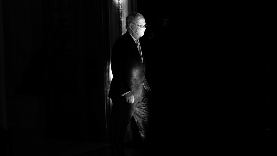 A black-and-white photo of Mitch McConnell wearing a face mask, surrounded by darkness