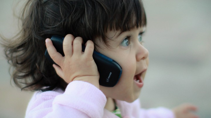 a small girl talking on a phone
