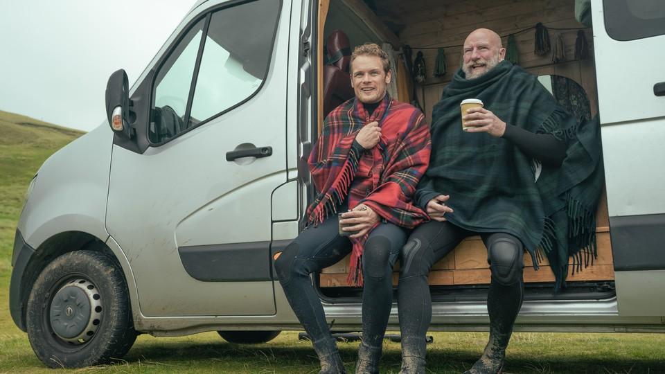 Two men in kilts sit in the open door of a van