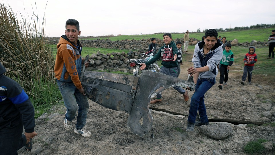 Children carry a part of a missile