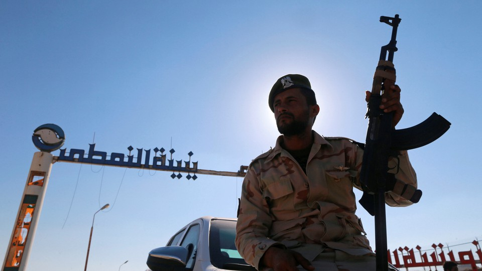 A member of Libyan forces loyal to eastern commander Khalifa Haftar holds a weapon as he sits on a car in front of the gate at Zueitina oil terminal, west of Benghazi, Libya, on September 14, 2016.