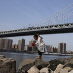 A photo of a child playing on the rocks under the Manhattan Bridge in Brooklyn.