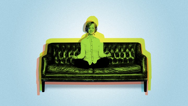 A woman meditating on a couch