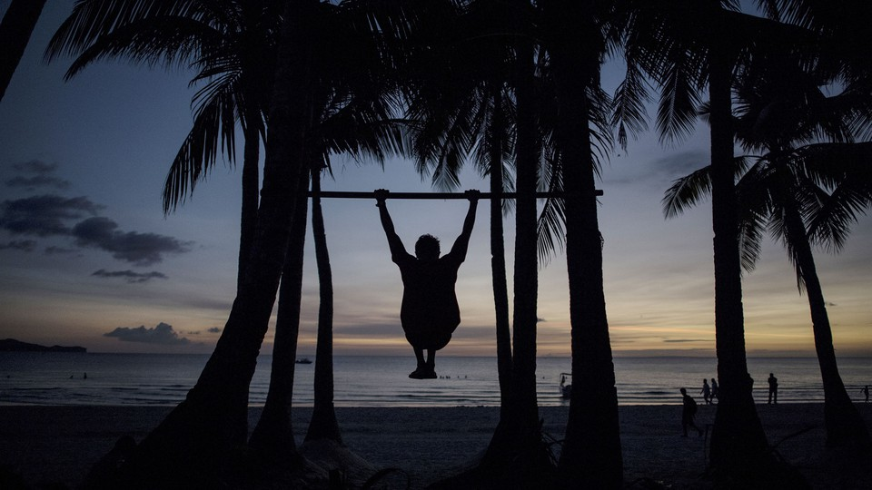 The silhouette of a man doing a pull-up on a beach in the Philippines.