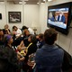 People crowd into a room to watch Christine Blasey Ford testify on TV.