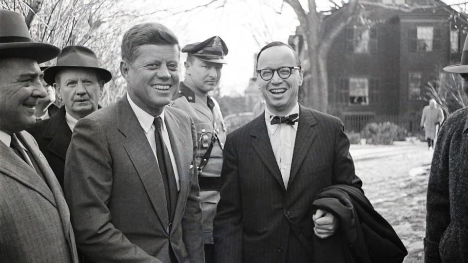 A black-and-white photograph of JFK and his biographer Arthur Schlesinger Jr. laughing in Boston winter, surrounded by a crowd of men