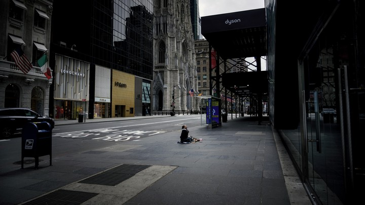 A homeless woman surrounded by luxury stores on 5th Avenue in New York City.