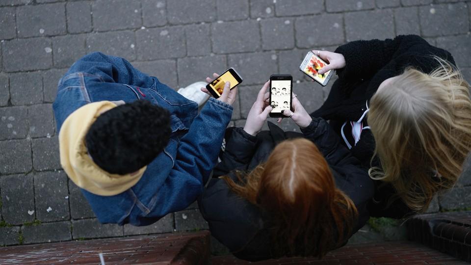 Three people looking at their phones