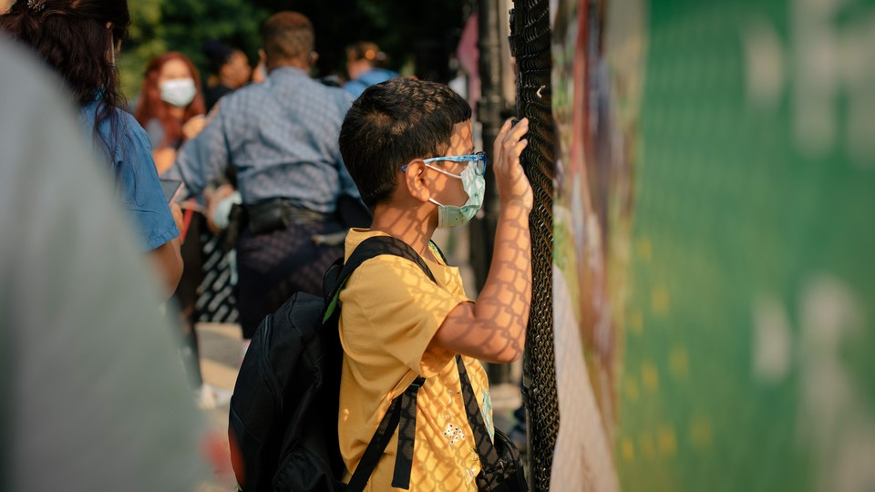 A student looks through a fence at a school.