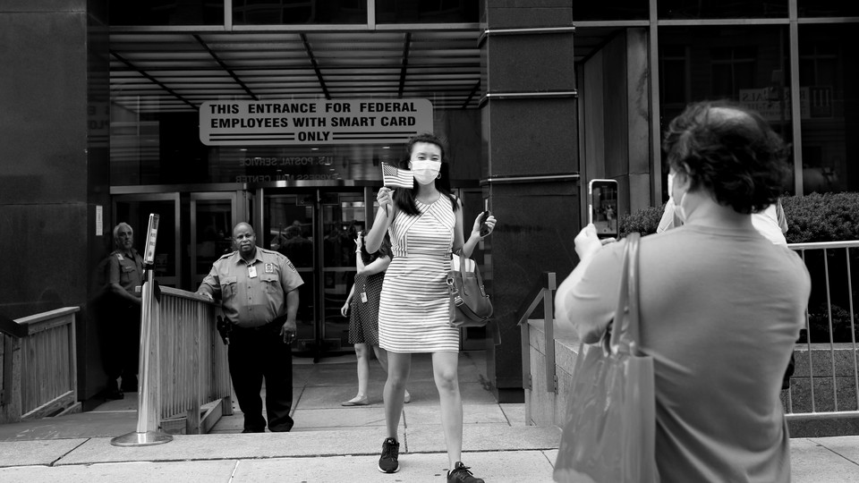 Amy's father takes her photo as she walks out of the USCIS building an American citizen.