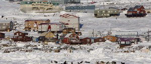 A snowmobiler rides past sled dogs on Frobisher Bay in Iqaluit, Nunavut, Canada.