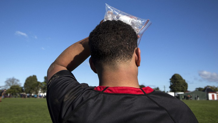 A soccer player holding a bag of ice to his head.