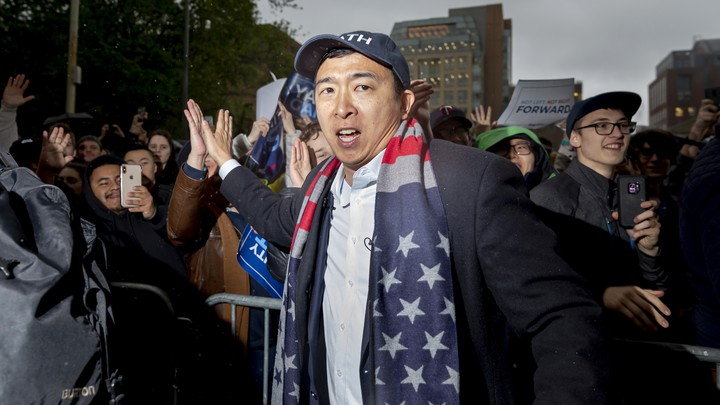 Andrew Yang high fives a supporter at a rally. An American flag is draped over his neck.