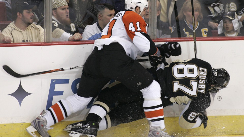 Sidney Crosby gets checked into the boards