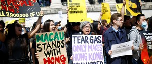 "Supporters of the Hong Kong protests hold signs reading ""Macau stands with Hong Kong"" and ""Tear gas only makes Hong Kong cry harder."""